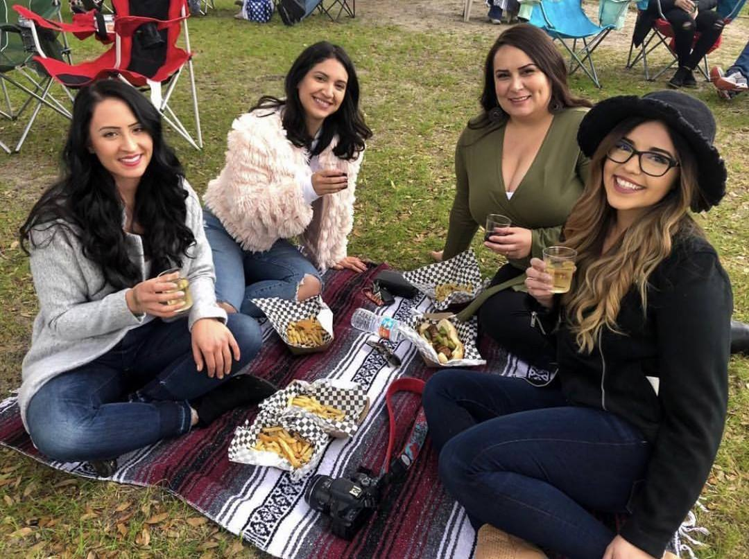Young women enjoying a glass of wine and food outside