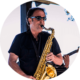 An entertainer on the outdoor festival stage playing saxophone.
